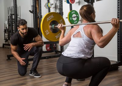 Female squatting with assistance of trainer