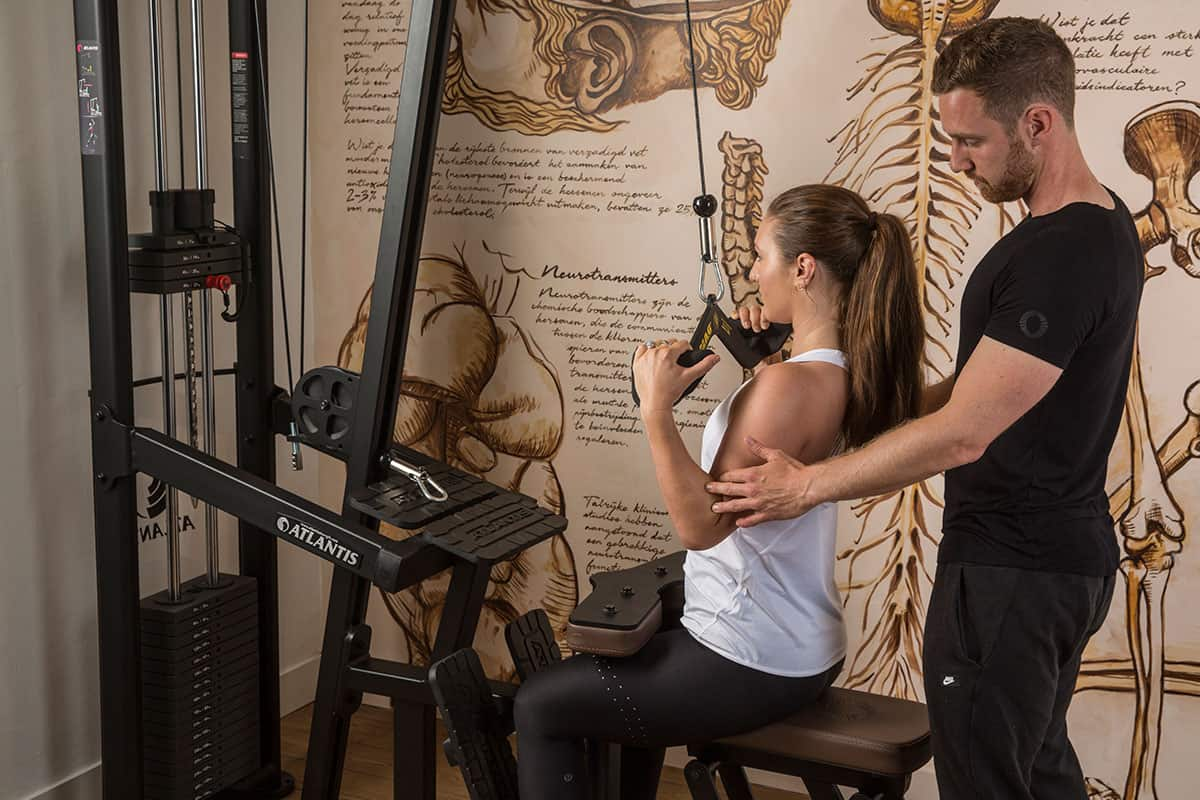 Female doing a lat pull, assisted by trainer